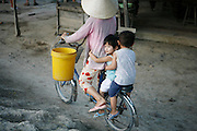 Mang Thit, Vietnam. March 17th 2007..Two kids and their mother in Mang Thit, a small village on a bank of the Mekong.