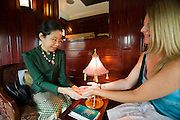 Eastern & Oriental Express. A passenger has her hands read by the Fortune Teller.