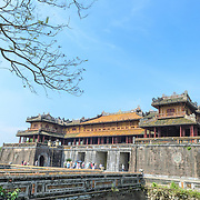 The Citadel Gate at the Imperial City in Hue, Vietnam. A self-enclosed and fortified palace, the complex includes the Purple Forbidden City, which was the inner sanctum of the imperial household, as well as temples, courtyards, gardens, and other buildings. Much of the Imperial City was damaged or destroyed during the Vietnam War. It is now designated as a UNESCO World Heritage site. Copyspace in the blue sky.