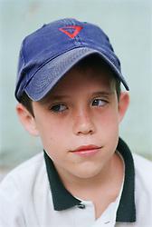 Portrait of young boy wearing baseball cap,
