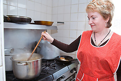 Cook stirring a large pan of stew in kitchen of Polish Social Club,
