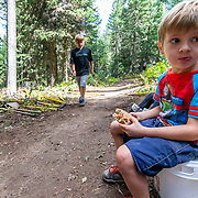 Micah Goodrich eating a sandwich while working on the Lithium singletrack in Wilson, Wyoming.