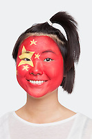 Portrait of happy young Asian woman with Chinese flag painted on face against white background