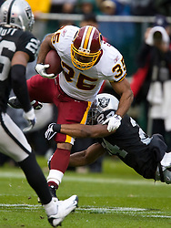 December 13, 2009; Oakland, CA, USA;  Washington Redskins running back Quinton Ganther (35) is tackled by Oakland Raiders safety Michael Huff (24) during the second quarter at Oakland-Alameda County Coliseum.  Washington defeated Oakland 34-13.