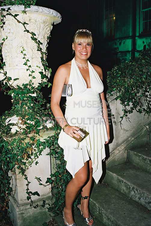 Woman in white evening dress standing outside, holding a glass of champagne, Posh at Addington Palace, UK, August, 2004