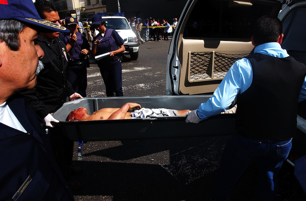 Police officers prepare to load the body of a man who was shot while attempting to rob El Banco Canarias de Venezuela, a bank in downtown Caracas, into a van. Of the 7 men who attempted to rob the bank, 2  were shot and killed.