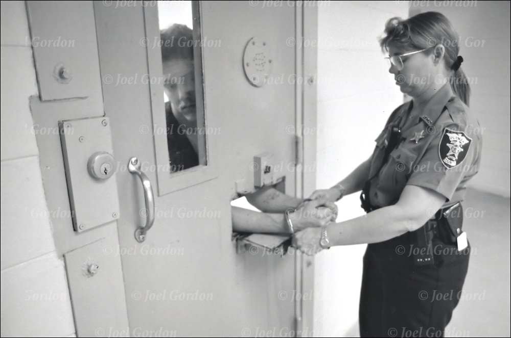 Female Correction officer placing handcuffs on male inmate through the opening of isolation cell door to transfer inmate back to jail general population in the Putnam County Jail FL