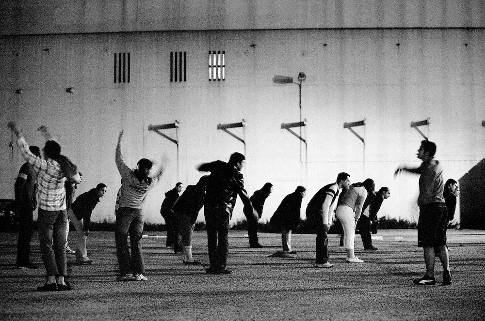 Rehearsing music and coreography. Each neighbourhood tries to surprise their opponents  by rehearsing in secret places like parking lots like this.