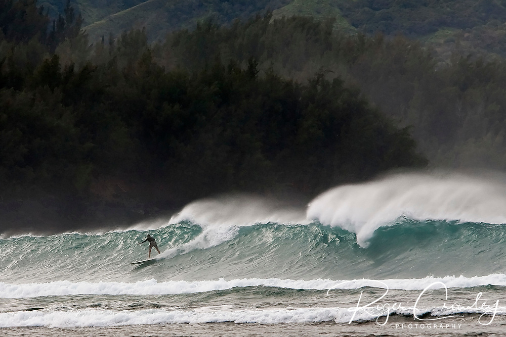 A surfer rides a large wave on Ke'e Beach in Hanalei Bay on the island of  Kaua'i, Hawaii