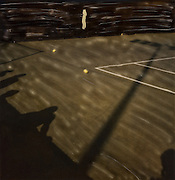 Shadows of spectators and light pole across outside court at US Tennis Open