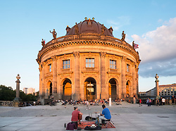 Late summer afternoon sun shining on Bode Museum with buskers and public relaxing on Museum Island in Berlin, Germany