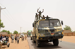 59722703 .Soldiers wave to residents after returning from battlefield, in El Rahad of Sudan's North Kordofan State May 28, 2013. Sudanese army announced on Monday that it has liberated the strategic area of Abu Karshula in South Kordofan State from rebels of the Revolutionary Front. May 28, 2013..UK ONLY