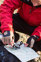 Male hiker using compass and map in forest