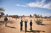 Children walk through a camp of internally displaced people near the village of Kouble by the side of the road on the highway outside of Diffa, Niger on February 17, 2016. The camp is made up of displaced people and refugees from villages along the border between Niger and Nigeria and who fled attacks from Boko Haram.