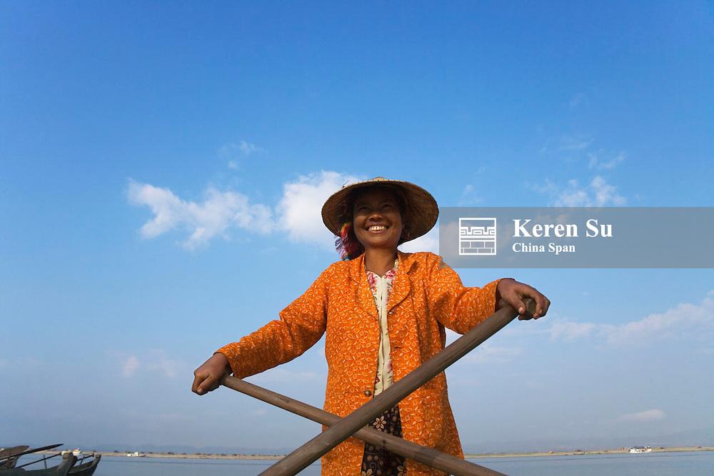 Girl wearing conical hat rowing boat on Taungthaman Lake, Amarapura, near Mandalay, Myanmar