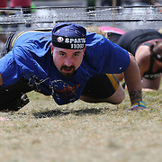 Marc Seyfried in action at the barbed wire crawl obstacle during the Reebok Spartan Race. Mohegan Sun, Uncasville, Connecticut, USA. 28th June 2014. Photo Tim Clayton