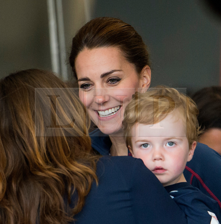 © London News Pictures. 26/07/2015. A young boy looks glum as his mother talks to CATHERINE, Duchess of Cambridge during a visit to Land Rover BAR (Ben Ainslie Racing) in Portsmouth, South Hampshire, as part of a visit to the America's Cup World Series with Prince William. Photo credit: Ben Cawthra/LNP