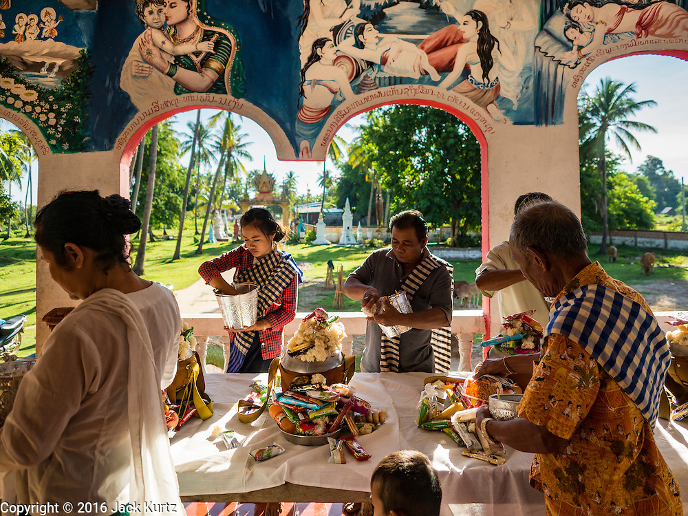 19 JUNE 2016 - DON KHONE, CHAMPASAK, LAOS: People present alms and offerings at a Buddhist temple in Don Khone village on Don Khone Island. Don Khone Island, one of the larger islands in the 4,000 Islands chain on the Mekong River in southern Laos. The island has become a backpacker hot spot, there are lots of guest houses and small restaurants on the north end of the island.    PHOTO BY JACK KURTZ