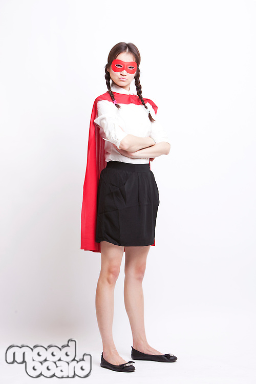 Portrait of young Asian woman wearing superhero costume against white background