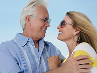 Middle-aged couple embracing and looking in eyes against sky