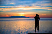 August 2, 2015: A photographer takes a photo of the sunset at Point Woronzof in Anchorage, Alaska.