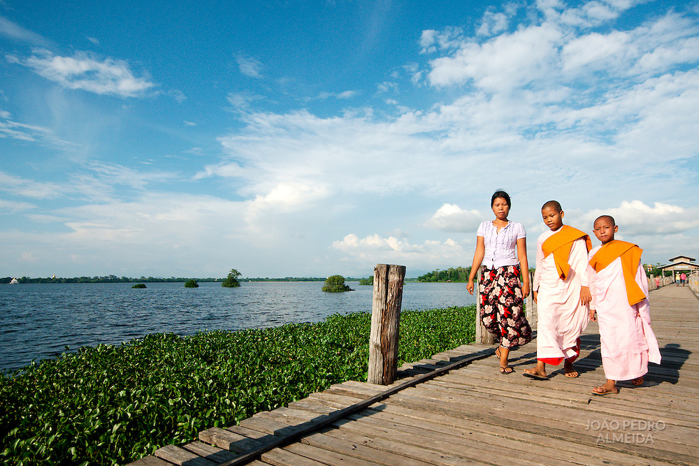 Young nuns crossing U Bein bridge