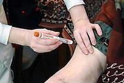 Nederland, Nijmegen, 3-3-2006..Een verpleegkundige van de thuiszorg geeft een injectie met een insulinepen aan een bejaarde, oudere vrouw...Foto: Flip Franssen