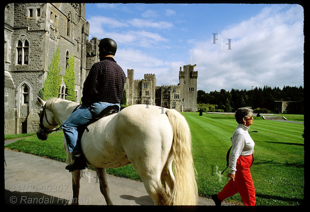 Man rides horse past woman walking outside Ashford Castle, an 83-room hotel counted among Ireland's finest; Cong, Ireland.