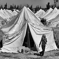 A Syrian refugee leaves a tent in a refugee camp in the town of Reyhanli, Turkey, Sunday, March 18, 2012. The number of Syrian refugees in Turkey is now about 17,000. March 2012.