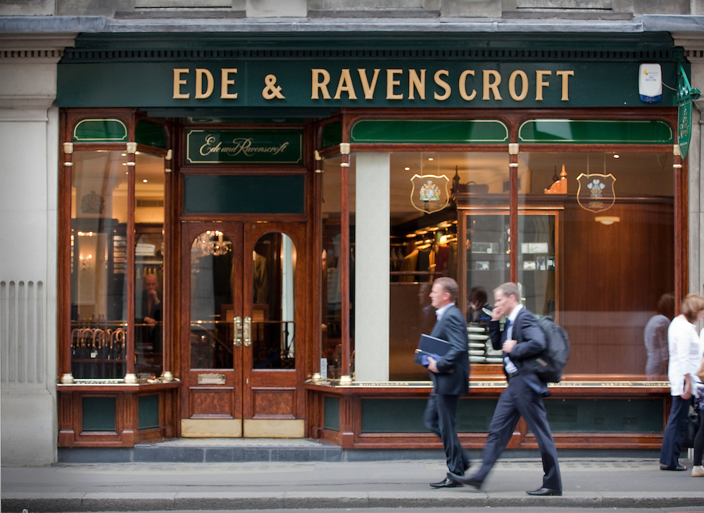 two office men in suits walking past pub in city of london