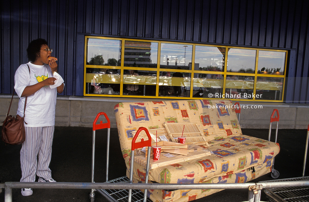 A lady shopper eats a hot dog alongside her new sofa bed and other home fittings, outside IKEA's Croydon shop in south London, on 21st August 1999, in London, England.