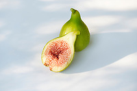 Freshly picked, ripe, organic Kadota figs with pink red pulp, artistic food still life isolated on white background