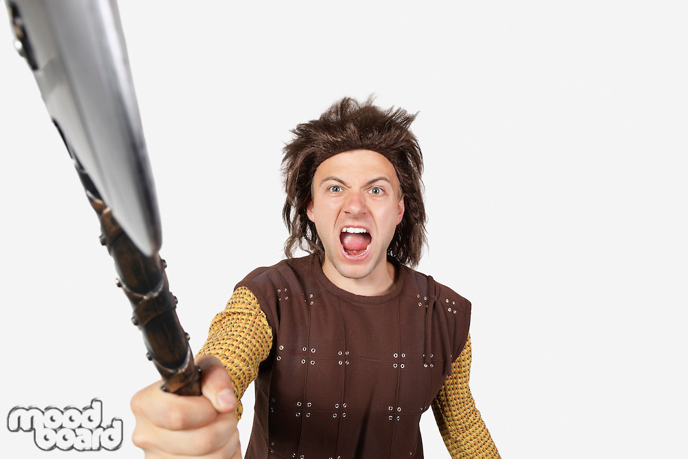 Portrait of angry man in caveman costume holding axe against gray background