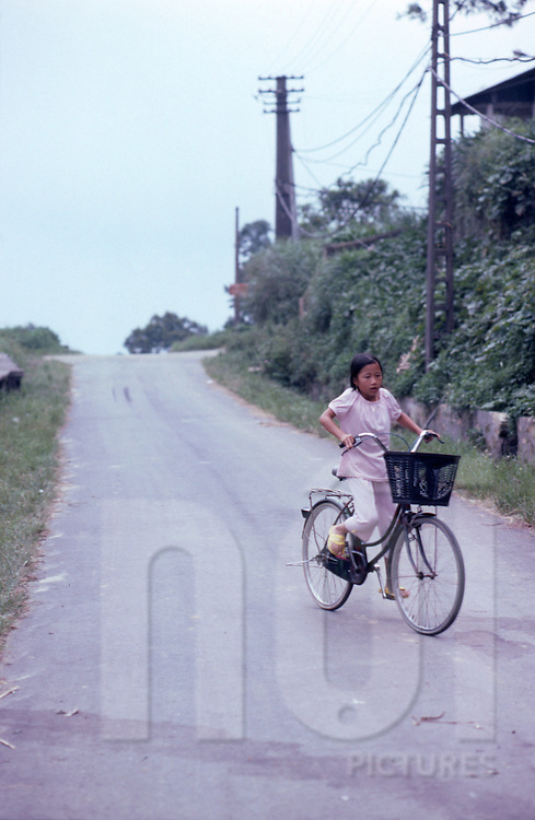 Young girl rides her bicycle along an empty road in Tam Dao, Vinh Phuc Province, Vietnam, Southeast Asia