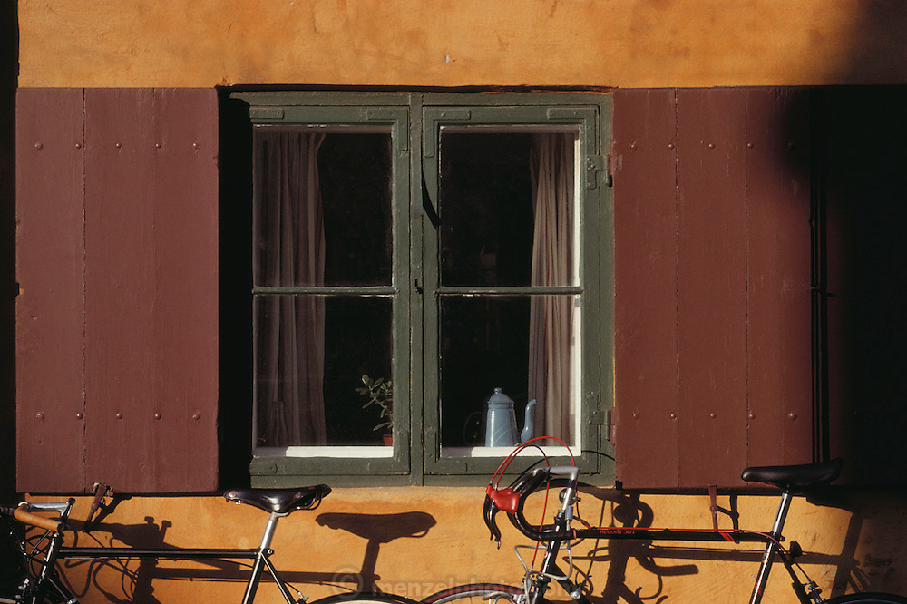 Kronprinzessegade. Bicycles leaning against a wall with a shuttered window in a row of yellow houses. Copenhagen, Denmark.