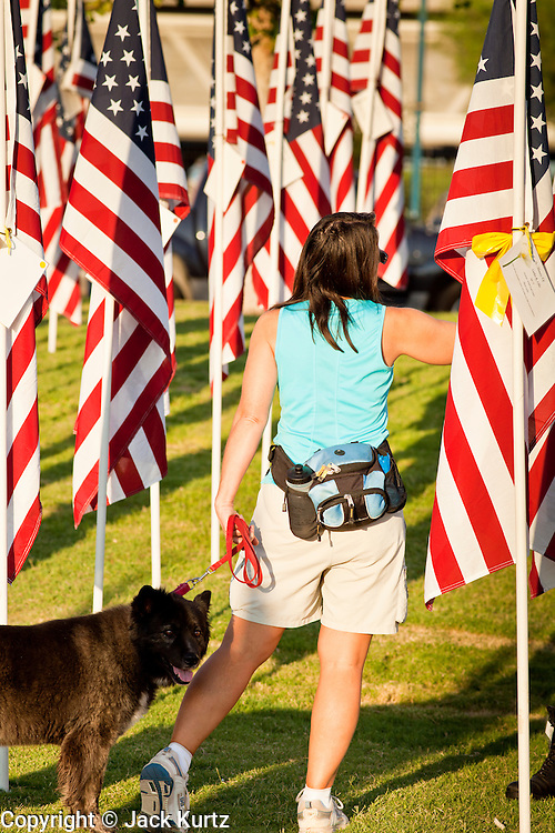"10 SEPTEMBER 2011 - TEMPE, AZ:     A woman walks through the ""Healing Field"" in Tempe, AZ, Saturday. The ""Healing Field,"" a display of 2,996 flags, one for each person killed in the September 11 terrorists attacks on the World Trade Center in New York City and Washington DC, have become an annual tradition in Tempe. The event is sponsored by the National Exchange Club.     PHOTO BY JACK KURTZ"