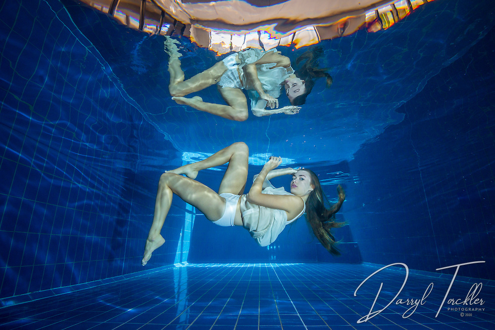 Beautiful woman wearing a short white dress suspended in a swimming pool.  New Zealand