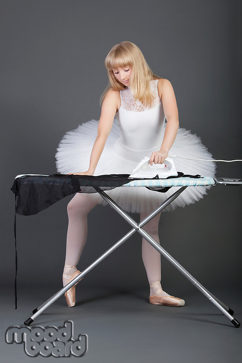 Young female ballet dancer ironing over grey background