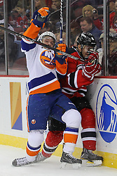 Jan 31, 2013; Newark, NJ, USA; New York Islanders center Keith Aucoin (10) hits New Jersey Devils defenseman Andy Greene (6) during the first period at the Prudential Center.
