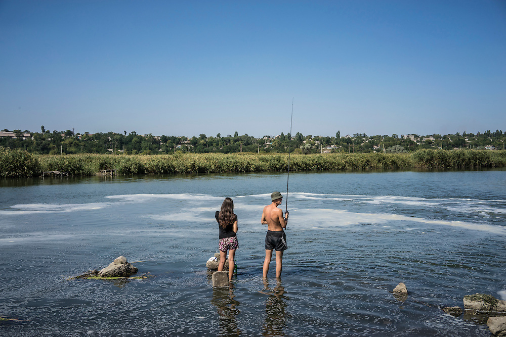 MARIUPOL, UKRAINE - AUGUST 31, 2015: A man fishes in the Kalmius River next to a pipe that discharges water from the Azovstal steel factory, located just across the street, in Mariupol, Ukraine. CREDIT: Brendan Hoffman for The New York Times