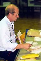 Postman sorting letters prior to delivering them on his walk ......