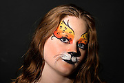 young teenage female model with elaborate tiger make up mask on black background model released studio shot