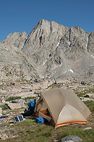 Portable solar charger charging smartphone at Backcountry camp in Indian Basin, Bridger Wilderness,  Wind River Range Wyoming