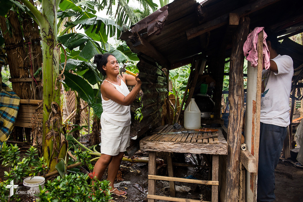 A woman repairs her home following damage from Typhoon Haiyan in Mayahag, Leyte Province, Philippines, on Saturday, March 15, 2014.LCMS Communications/Erik M. Lunsford
