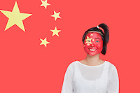 Portrait of young Asian woman with painted face smiling against Chinese flag