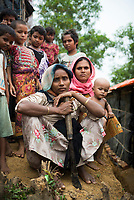 A group of Rohingya women and children congregate outside their plastic and bamboo shelters at Kutupalong refugee camp in Bangladesh. The Rohingya, most of whom are Muslim, are from Myanmar but effectively denied citizenship under Burmese law. They are thus one of the largest stateless groups in the world.  (October 29, 2017)