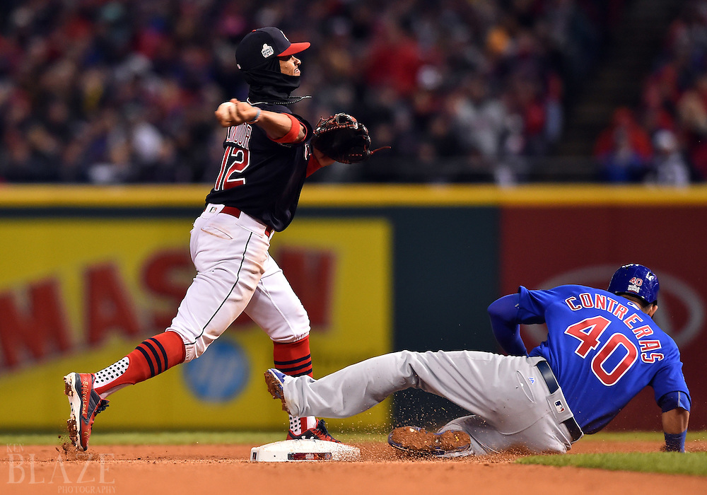Oct 26, 2016; Cleveland, OH, USA; Cleveland Indians shortstop Francisco Lindor (12) turns a double play over Chicago Cubs catcher Willson Contreras (40) in the fourth inning in game two of the 2016 World Series at Progressive Field. Mandatory Credit: Ken Blaze-USA TODAY Sports