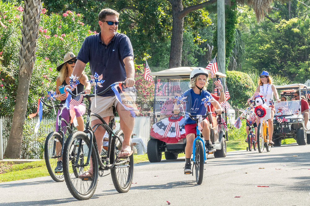Families take part in the annual Independence Day golf cart and bicycle parade July 4, 2019 in Sullivan's Island, South Carolina. The tiny affluent Sea Island beach community across from Charleston holds an outsized golf cart parade featuring more than 75 decorated carts.