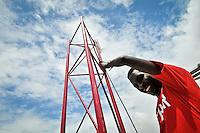 Sam, an Kenyan engineer with Somalia Wireless, installs a wireless reciever antenna on top of Benadir University. Mogadishu, Somalia.