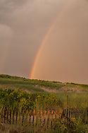 A sunset rainbow paints an arc of color over the dunes at Head of thet Meadow Beach.